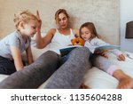 mother reading bedtime story to ... | Shutterstock . vector #1135604288
