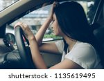 Small photo of Stressed woman drive car feeling sad and angry. Asian girl tired, fatigue on car. Driver tired drowsy, drink don't drive concept. Sleepy and drunk female hangover. Illegal law driver license.