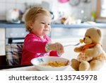 adorable baby girl eating from...   Shutterstock . vector #1135745978