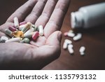 Small photo of Macro Of A Male Hand Holding Several Pills With Prescription Bottle And More Pills In Background - Taking Too Many Pills Concept