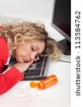 Exhausted woman asleep at work - with spilled energy pills - stock photo