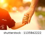 mom holds the baby by the hand   Shutterstock . vector #1135862222