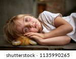 Small photo of Portrait of unfortunate stray kid lying on the board in the dirty alley, shallow depth of field.