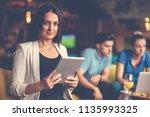 smiling young women using...   Shutterstock . vector #1135993325