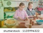 smiling schoolgirls learning to ... | Shutterstock . vector #1135996322