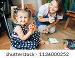 happy mom and her child ... | Shutterstock . vector #1136000252
