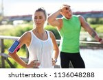 young couple jogging in park | Shutterstock . vector #1136048288
