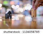 hand choosing mini wood house... | Shutterstock . vector #1136058785