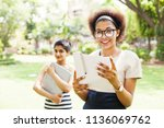 two young female students... | Shutterstock . vector #1136069762