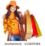 Woman wearing autumn overcoat and hat holding shopping bag. - stock photo