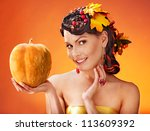 Woman holding autumn pumpkin and leaves. - stock photo