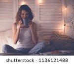 pretty woman drinking coffee... | Shutterstock . vector #1136121488