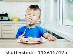 hungry baby eating dumplings in ... | Shutterstock . vector #1136157425