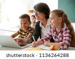 female teacher helping children ... | Shutterstock . vector #1136264288