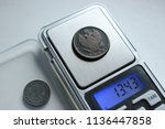 weighing the copper coin of the ... | Shutterstock . vector #1136447858