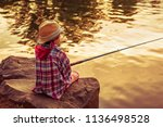 A Fisherman Boy Sits With A...