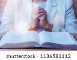 Small photo of close up of woman hands praying to God while reading bible on wooden table in morning devotion, Christian