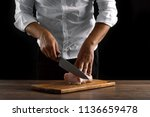 the chef cuts a piece of fresh... | Shutterstock . vector #1136659478