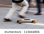 motion blur picture of an unrecognizable boy running with his skateboard - stock photo