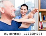 physio doing shoulder exercises ... | Shutterstock . vector #1136684375
