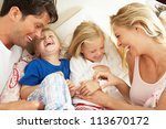 family relaxing together in bed | Shutterstock . vector #113670172