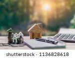 house placed on coins. notebook ... | Shutterstock . vector #1136828618