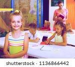 smiling junior girl standing... | Shutterstock . vector #1136866442