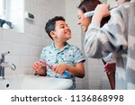 Small photo of Children are brushing their teeth in the bathroom at home. The mother is checking the little boy's mouth to make sure he has brushed properly.