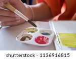 student's hand with brush... | Shutterstock . vector #1136916815