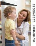 doctor pediatrician measures... | Shutterstock . vector #1136950358
