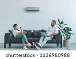 couple turning on air... | Shutterstock . vector #1136980988