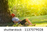 a young man is sleeping under... | Shutterstock . vector #1137079028