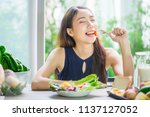 young asian woman happy eating... | Shutterstock . vector #1137127052