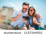 happy couple paying on line... | Shutterstock . vector #1137244502