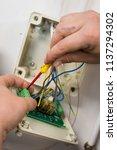 an electrician wiring in an... | Shutterstock . vector #1137294302