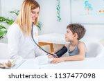 pediatrician measuring boy s... | Shutterstock . vector #1137477098
