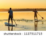 Men  friends paddling on a sup...