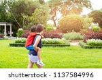 mother and son piggyback in the ... | Shutterstock . vector #1137584996