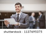 young businessman with a tablet ...   Shutterstock . vector #1137695375