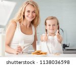 child with mother drinking milk.... | Shutterstock . vector #1138036598