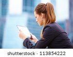Businesswoman working on digital tablet out of office overlooking cityscape - stock photo