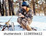 Female hunter preparing food with a portable gas burner in a winter forest. Bushcraft, hunting and people concept - stock photo