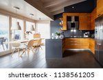 Small photo of Front view modern wooden kitchen with table and chairs. Nobody inside