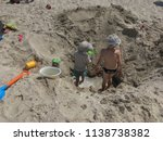 children dig a hole in the sand ... | Shutterstock . vector #1138738382