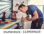 man working on a new kitchen... | Shutterstock . vector #1139059625