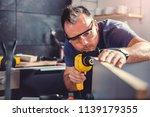 man working on a new kitchen... | Shutterstock . vector #1139179355