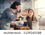 mother and daughter tasting... | Shutterstock . vector #1139265188