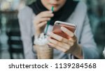 Stock photo beautiful muslim girl with hijab using smartphone while drinking at cafeteria business woman using 1139284568