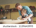 father and son sawing a plank... | Shutterstock . vector #1139643995