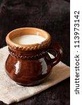 Fresh milk in a ceramic mug on a linen napkin. - stock photo